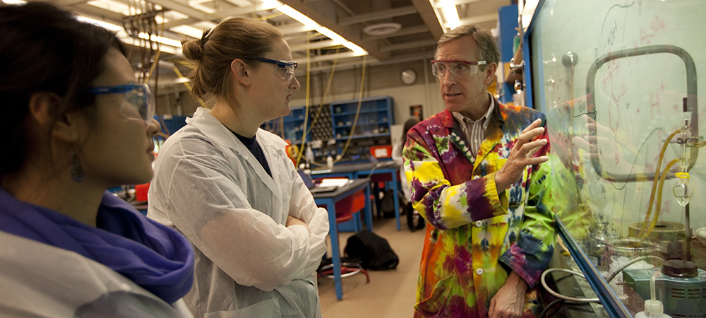 Students talk with a professor in a science laboratory