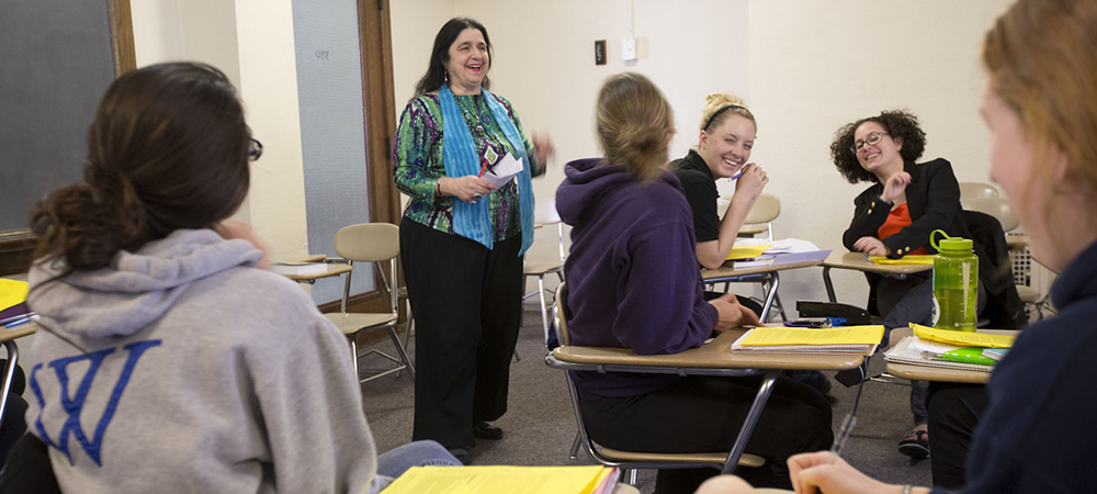 Students in classroom laugh with lecturer