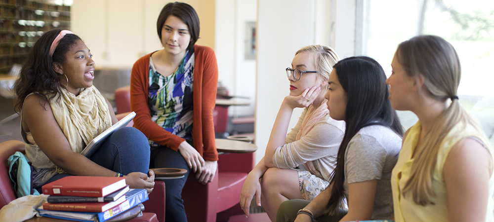 A group of students talking in the Clapp Library