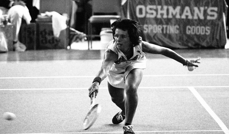 Billie Jean King bends down low to send the ball back over the net during the match with Bobby Riggs in the Astrodome