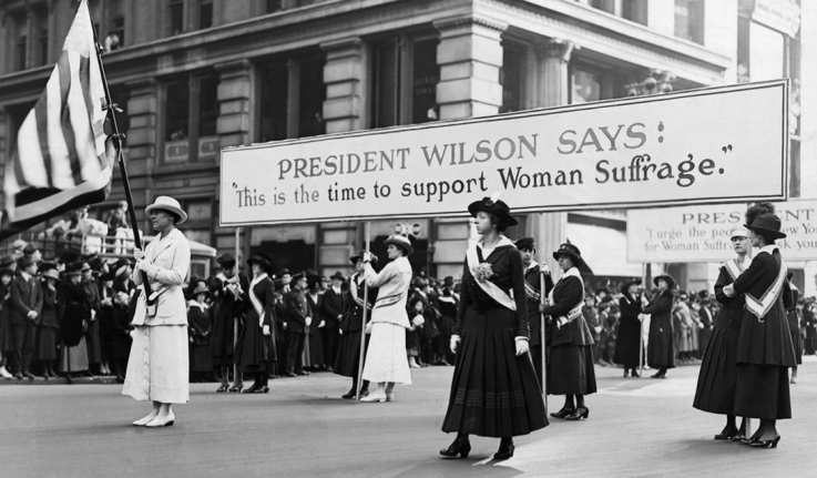 """Suffragists march with a sign that reads, """"President Wilson says: 'This is the time to support women's suffrage.'"""
