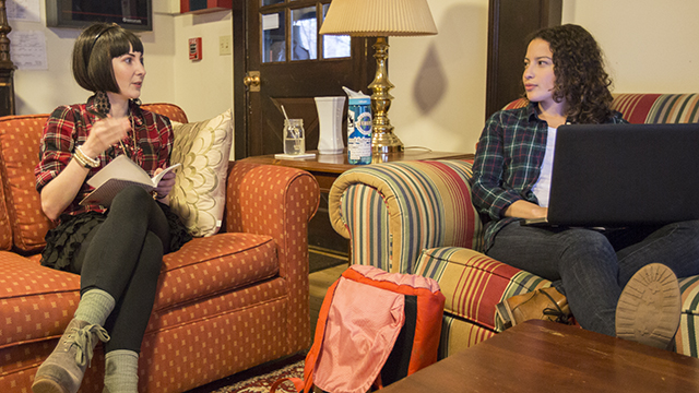 Two students having a conversation in a living room of a dorm.