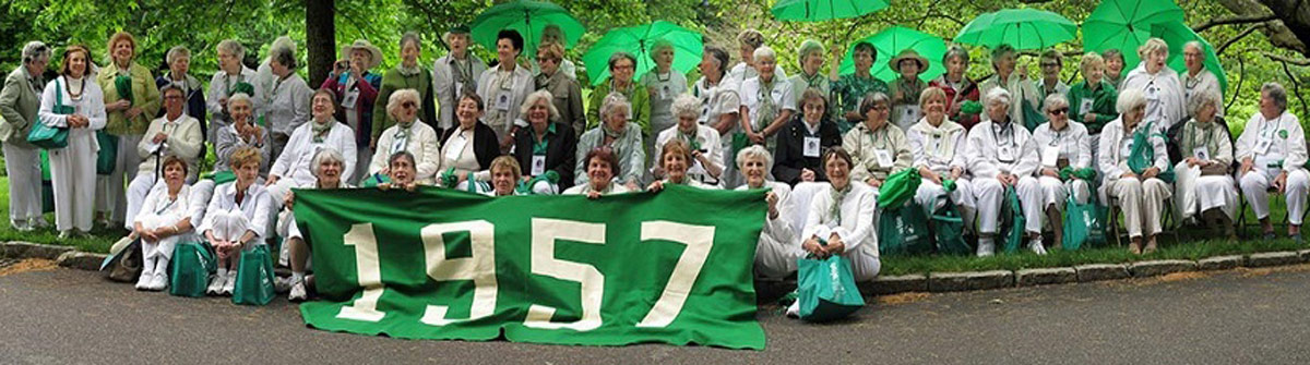 The green class of 1957's reunion photo. They hold a banner that reads 1957.
