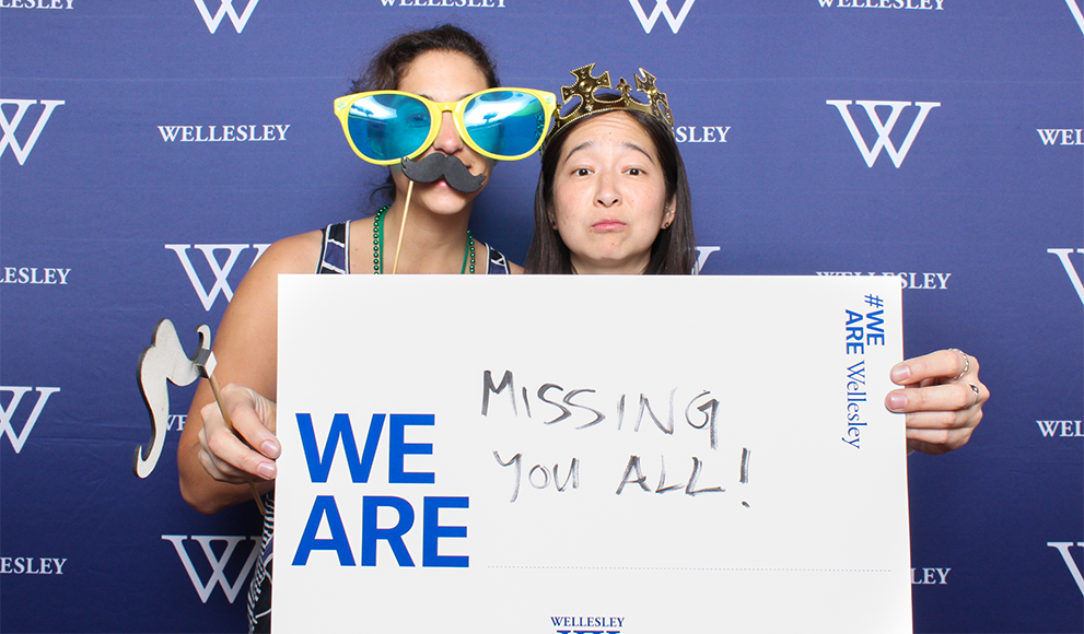 """Alumnae hold a sign during the reunion photo both reading """"We Are Missing You All"""""""