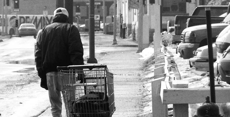 A man pulls a shopping cart in the snow. Changes to government safety-net programs meant more hardships for low-income families during the Great Recession.