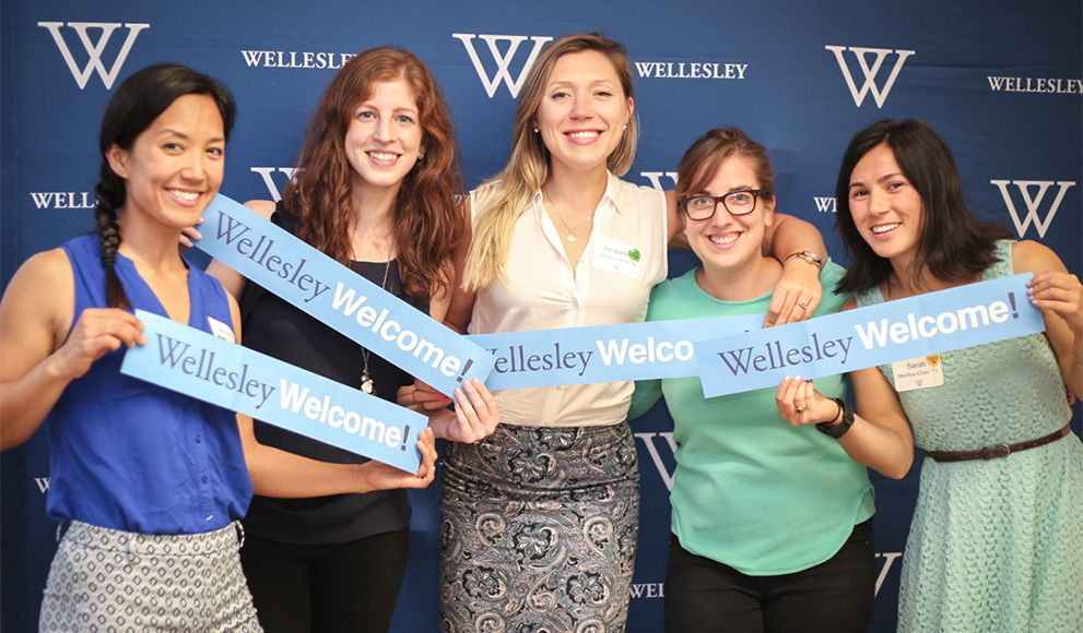 "Alumnae hold ""Wellesley Welcome"" signs in front of a blue backdrop"
