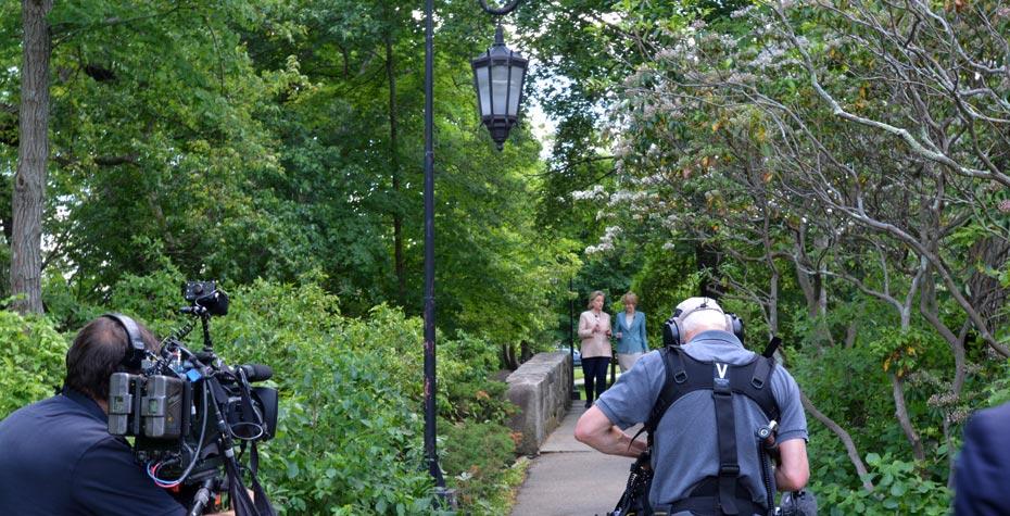 Jane Pauley and Hillary Clinton stJane Pauley and Hillary Clinton stroll on footbridge near Lake Waban as crew filmsroll on footbridge near Lake Waban as crew films