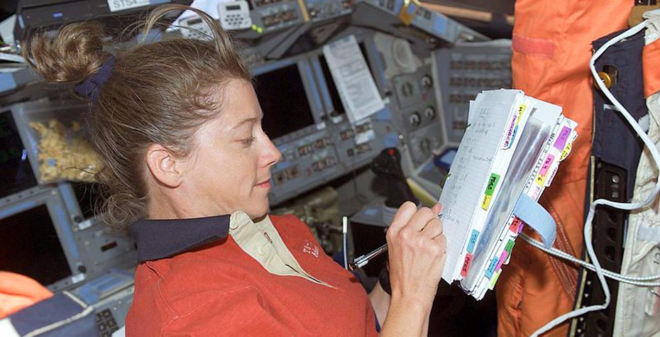 Pam Melroy in space, writing in notebook, 2007