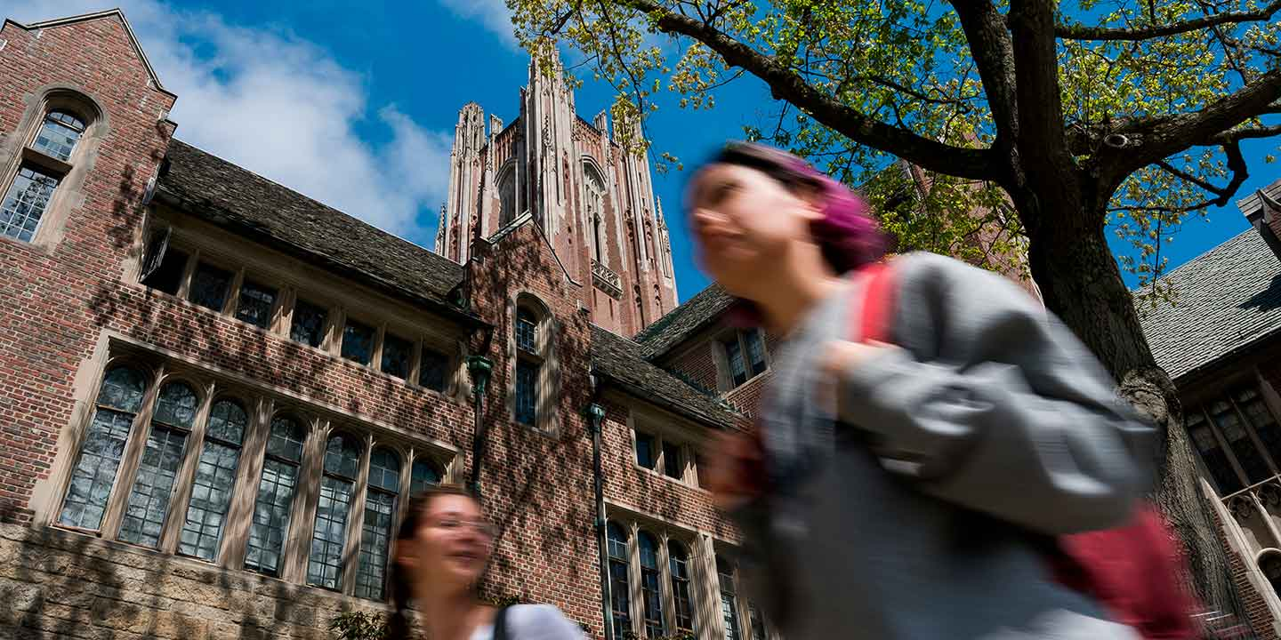 student walking underneath the stone tower