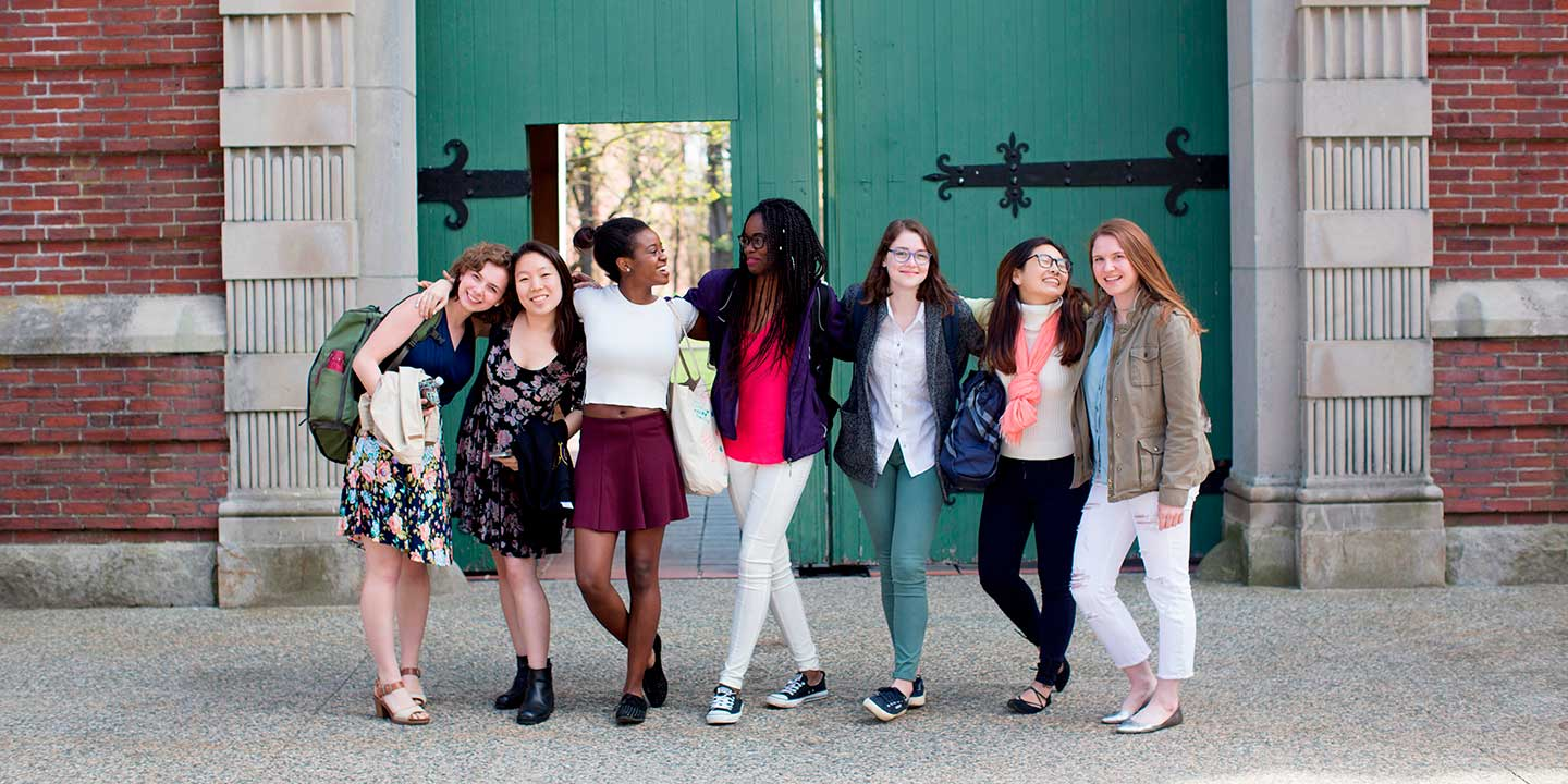 students standing in front of a green door in the quad