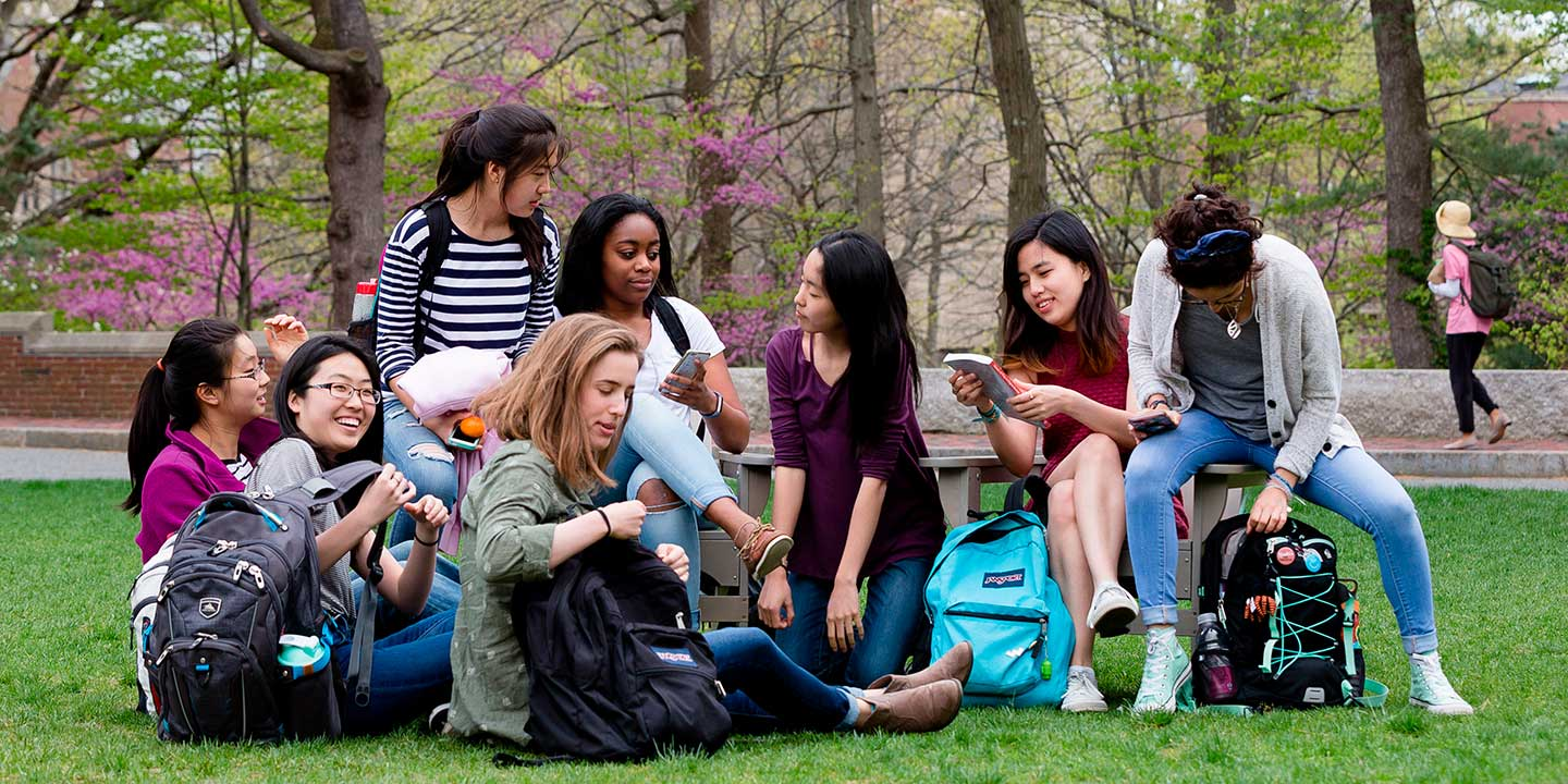 students gather around a laptop
