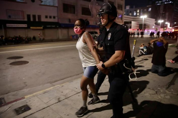 A Los Angeles police officer arrests a woman on May 31 during protests over the death of George Floyd. (Jae C. Hong/AP)