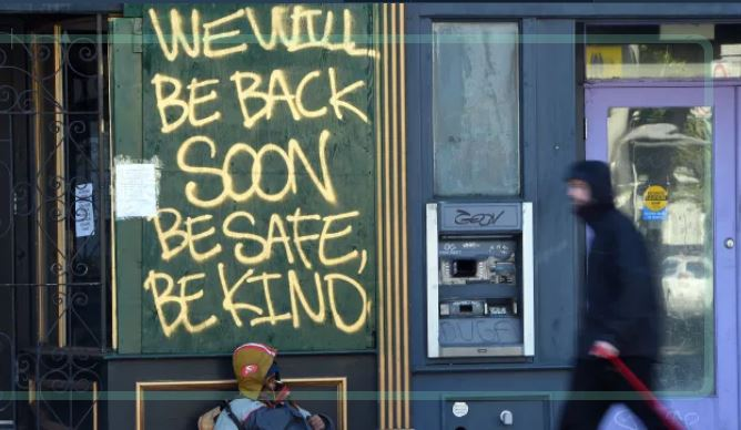 """A boarded-up shop is painted with the words """"We will be back soon, be safe, be kind"""""""