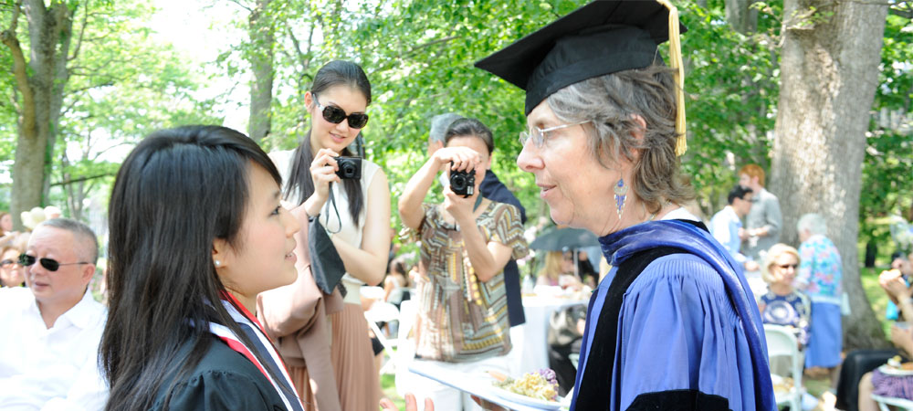 a student speaks with a professor at commencement