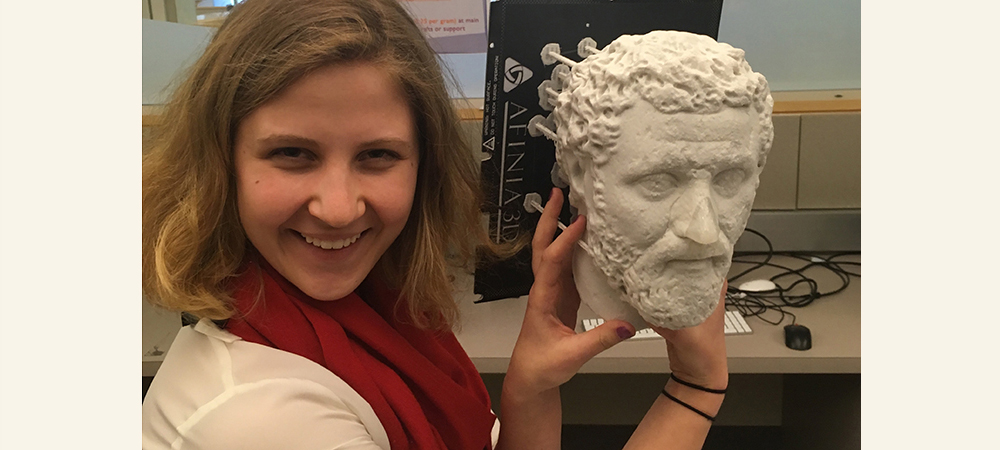 Student holding a Greek statue head replica next to her head and smiling