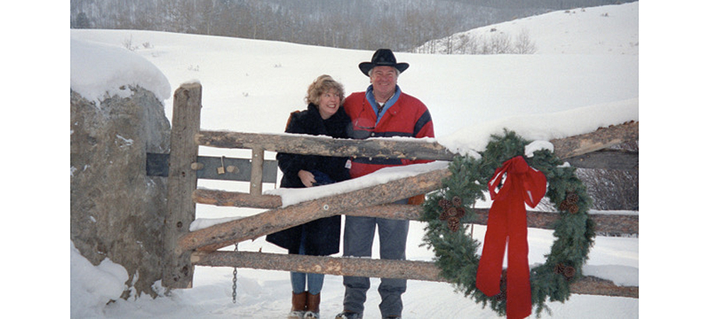 Betsy and Bud in front of a snowy landscape and behind a gate with a Christmas wreath