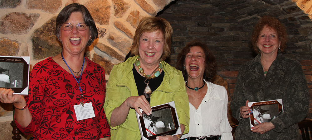 Betsy and three other women holding new picture frames and smiling