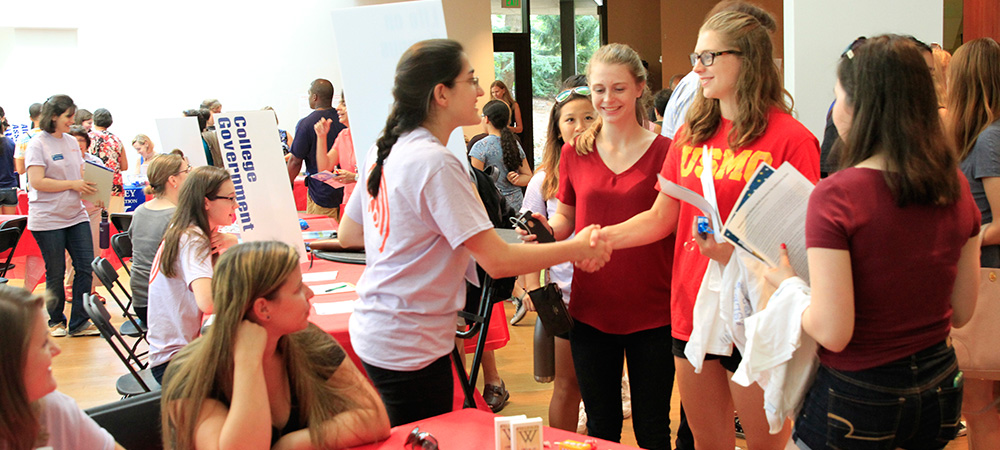 Students greeting each other at an organization fair