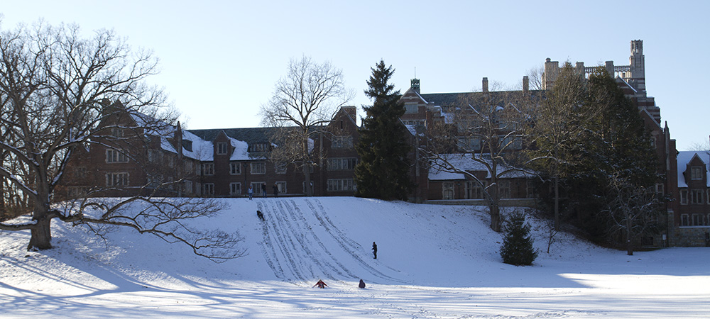 Students sledding down the snowy hill