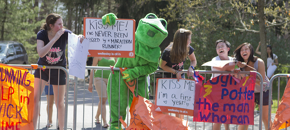 Students cheering on the runners in frog costumes and with creative signs