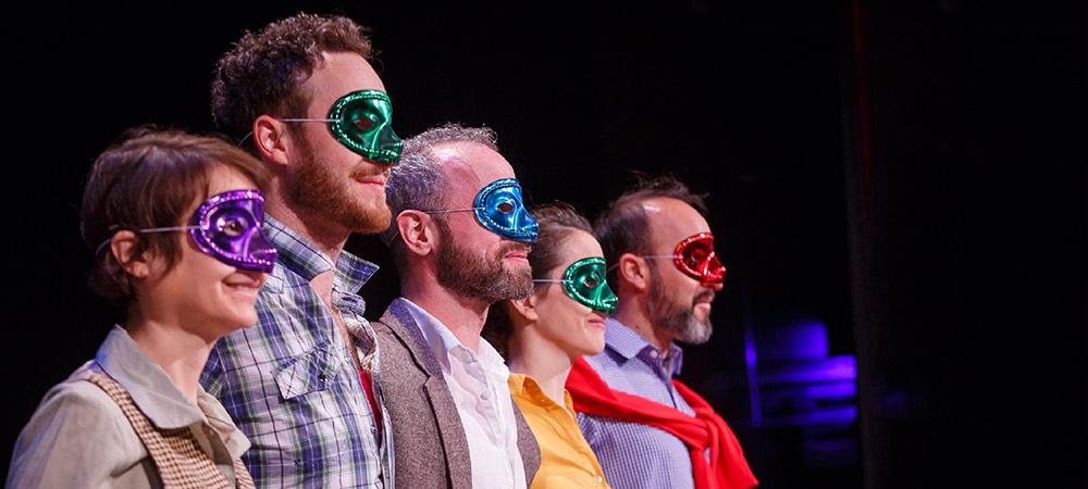 actors onstage wearing masks