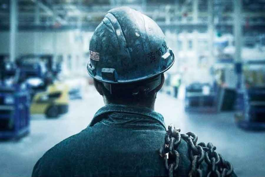 image of the back of a head of a person standing in a factory
