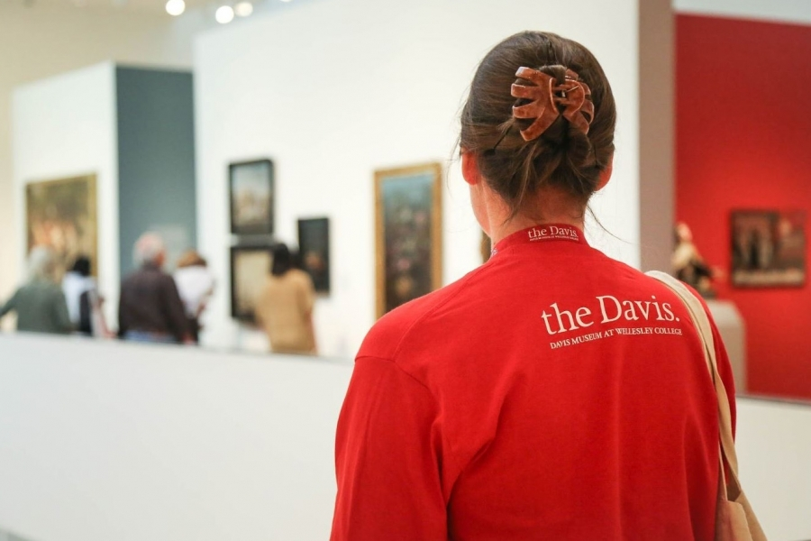 student wearing a Davis Museum t-shirt while standing in a gallery