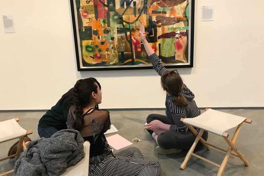 image of three people sitting on the floor in a Davis Museum gallery and looking at an abstract painting