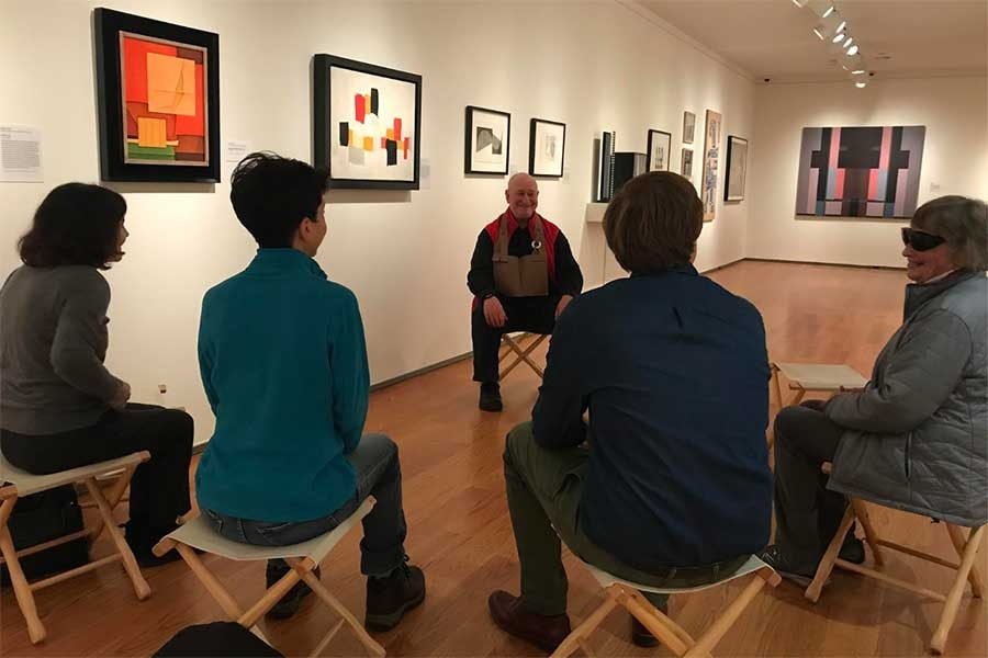A group of 5 people sitting in a gallery at the Davis Museum.