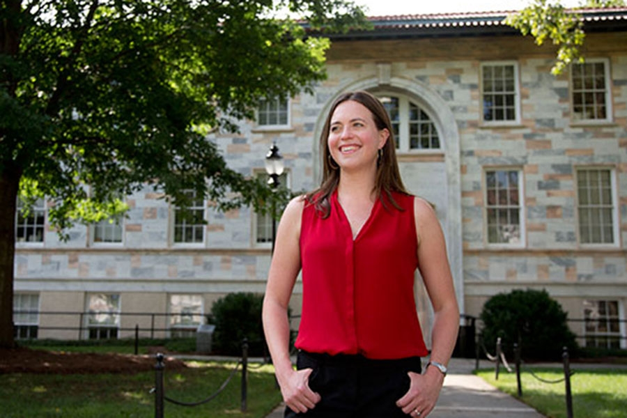image of a woman wearing a red shirt standing in front of an academic building