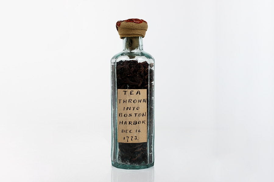 """image of a glass bottle containing dry tea. the bottle has a label that reads """"Tea thrown into Boston Harbor Dec. 16, 1776"""""""