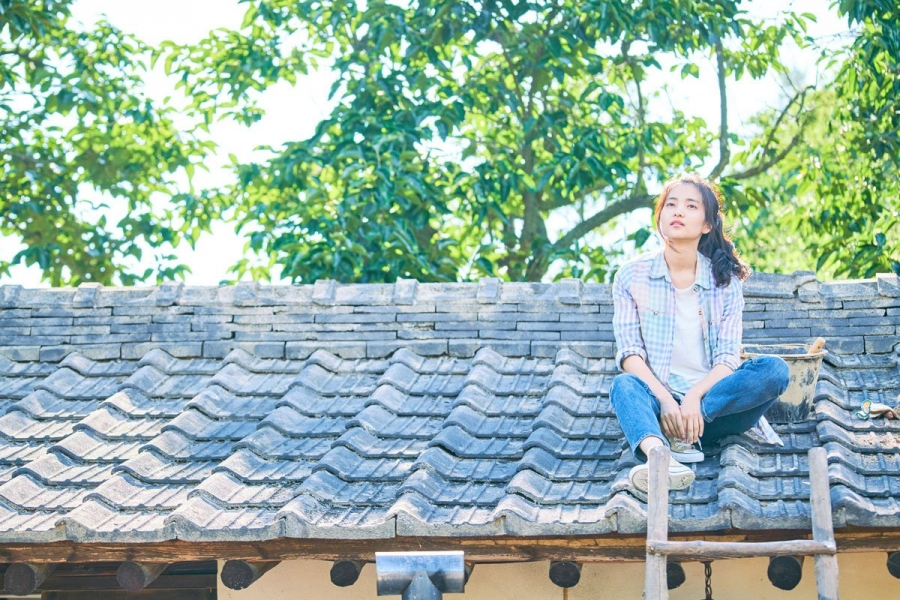 girl sitting on a roof in Little Forest