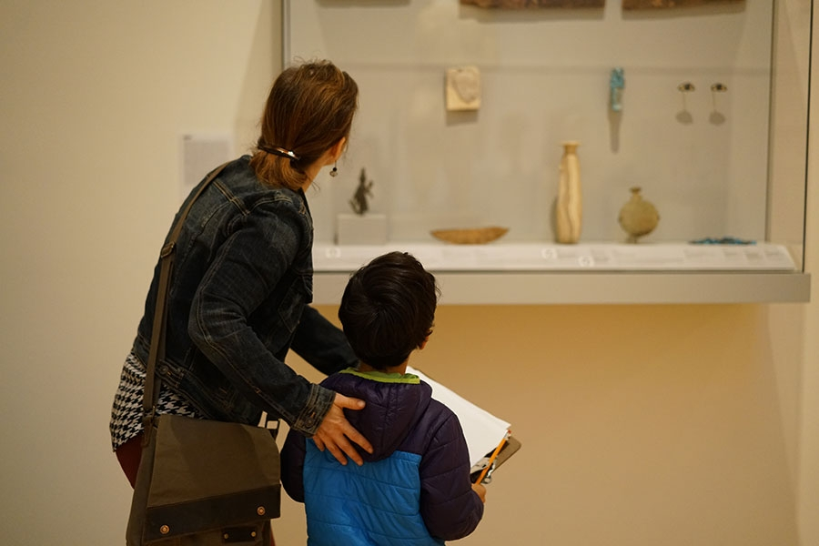 From behind, a woman and child look at a gallery exhibit at the Davis Museum