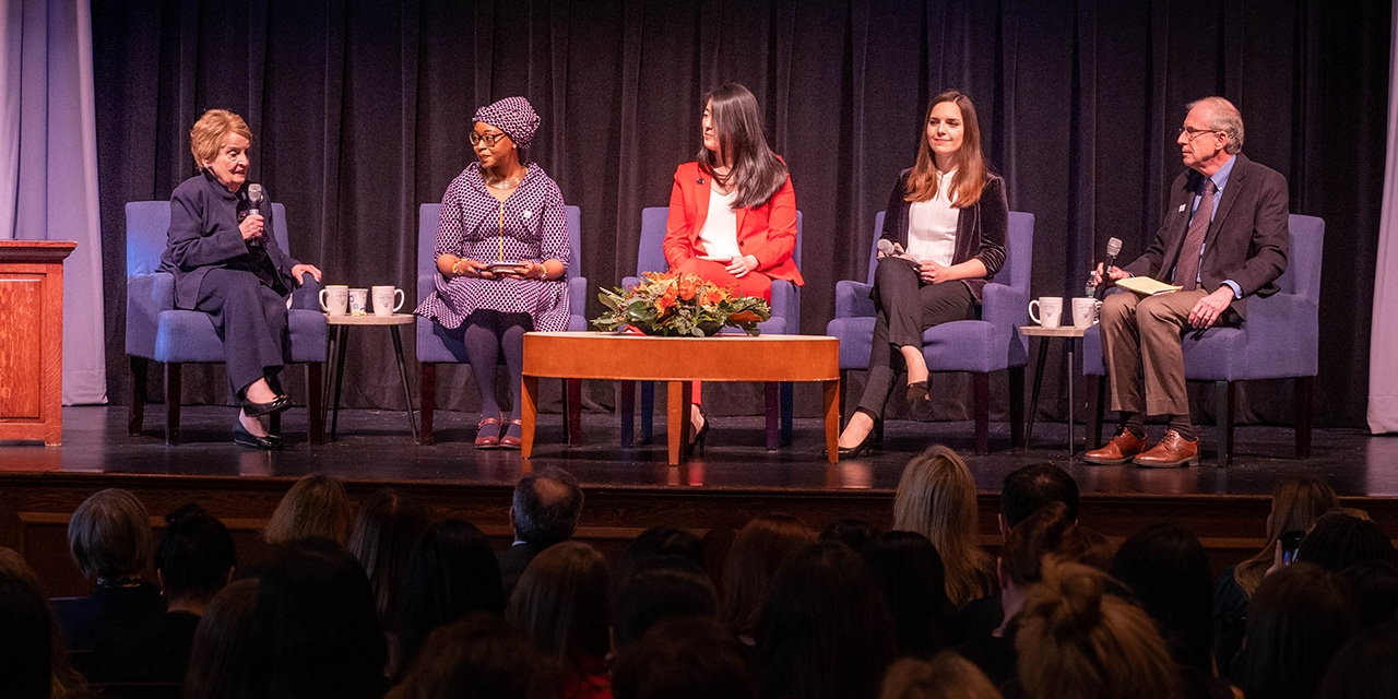 A panel of students sit with Madeleine Albright on stage.