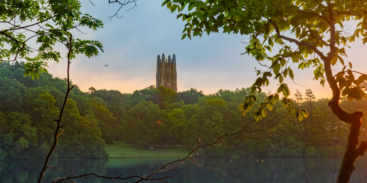 Dawn on Wellesley College's campus with Galen Stone Tower and Lake Waban in the background.