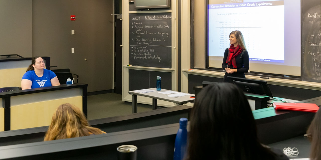 A professor stands at the front of a classroom, teaching.