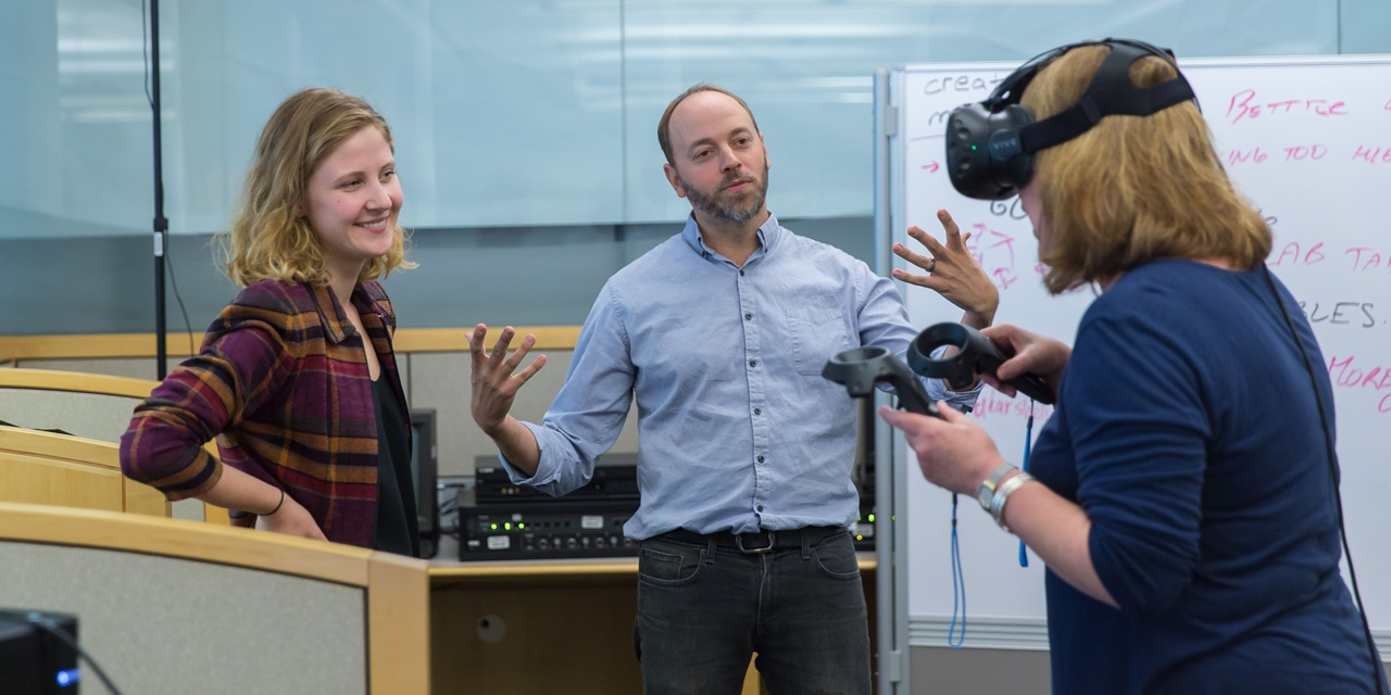 Knapp intern Kamile Lukosiute and Prof. Adam Van Arsdale watch as a user demos their human evolution virtual reality experience