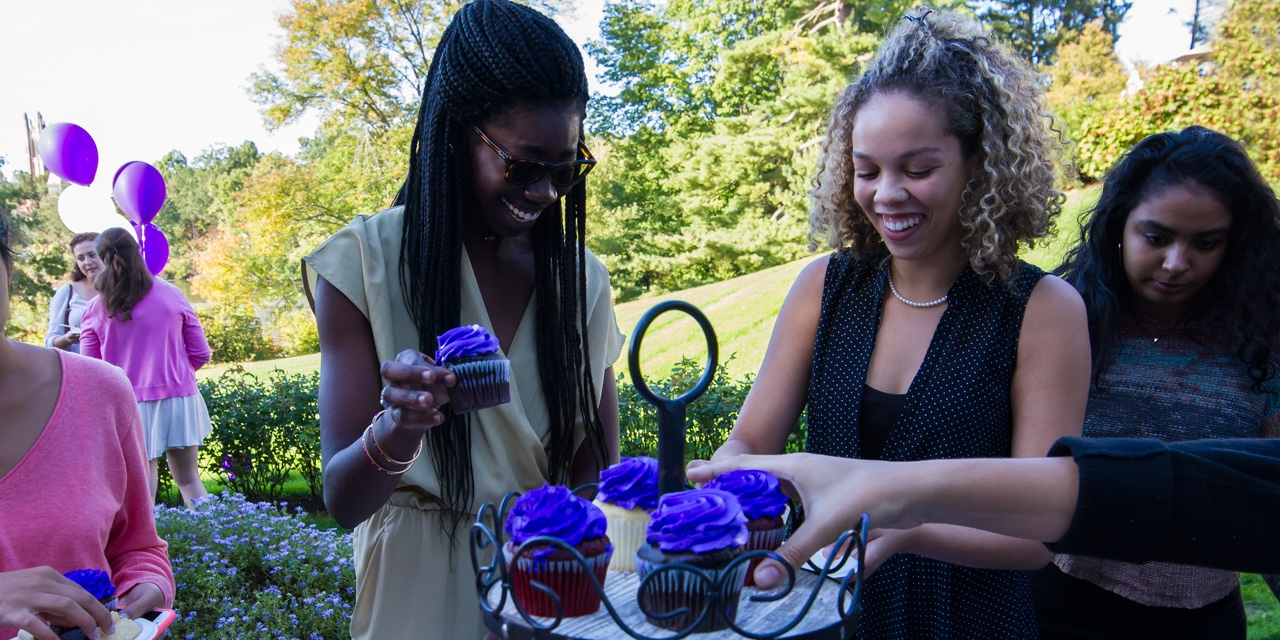 "The ""purple"" Class of 2018 enjoy purple cupcakes at the annual senior class reception."