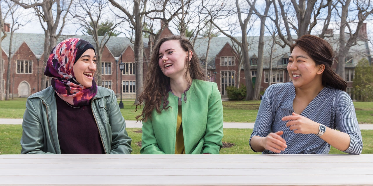 Three Wellesley students who won the Watson Fellowship sit on campus, laughing.