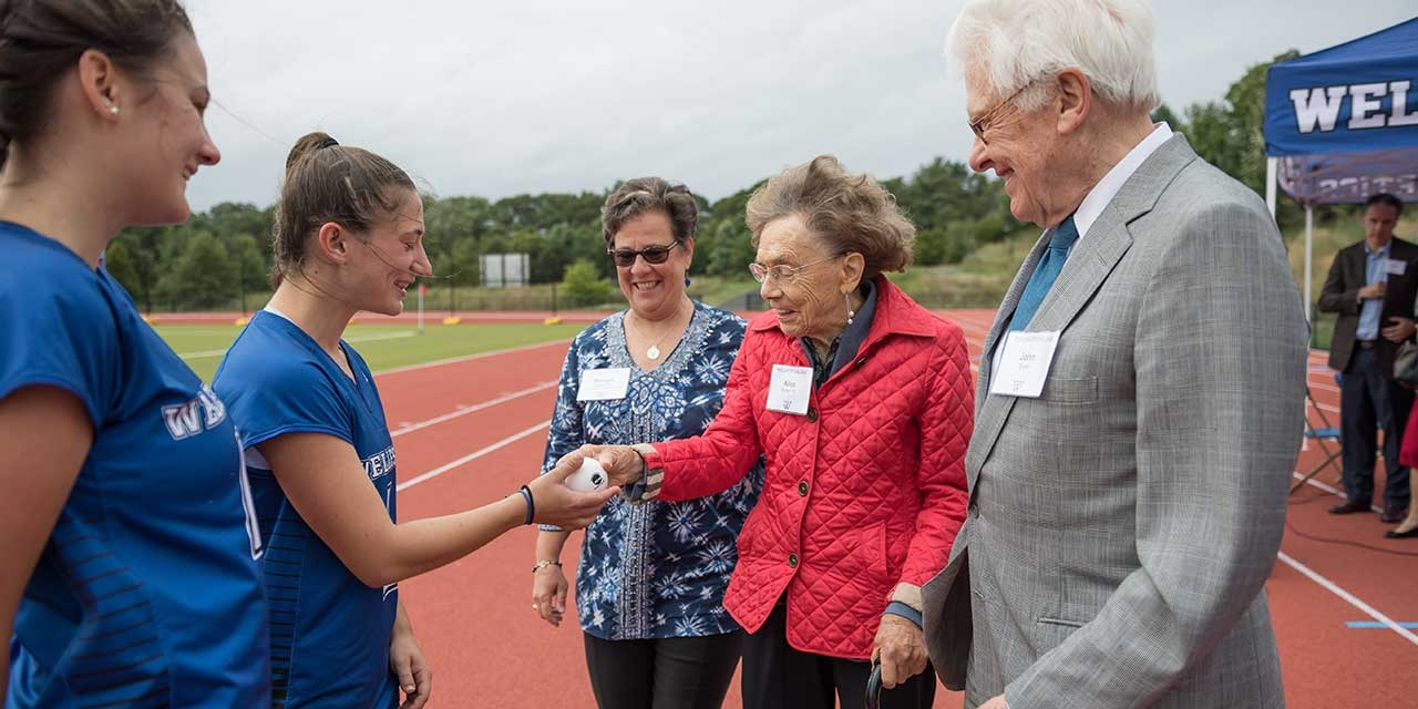 The donors of the turf field talk with students on the new track.