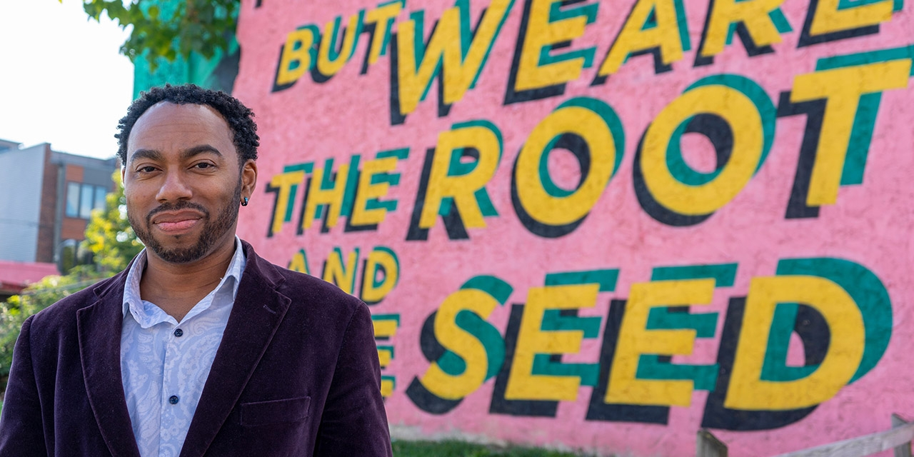 """A professor stands in front of public art that reads """"we are the root and the seed."""""""