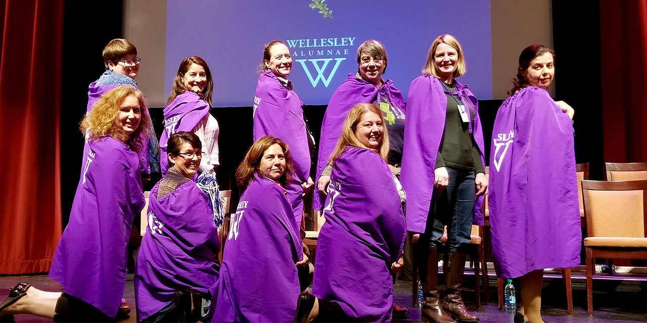 A group of women stand on stage wearing purple capes.