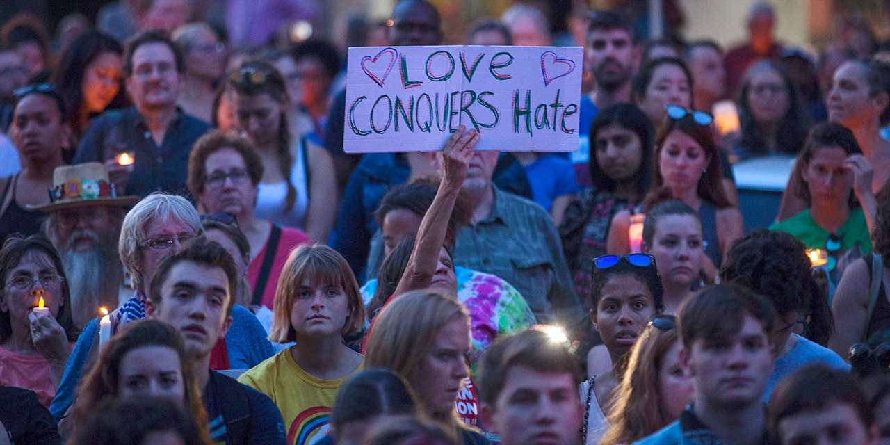 "Among a crowd gathered for a vigil, a woman holds a sign that says, ""Love Conquers Hate."""