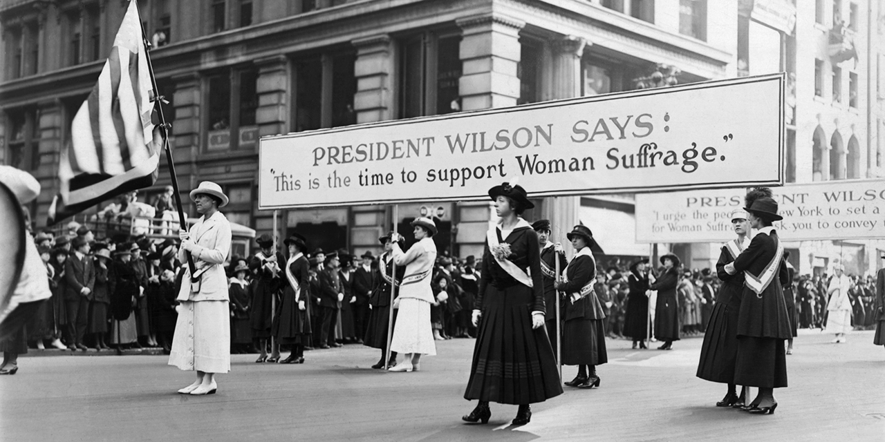 "Suffragists march with a sign that reads, ""President Wilson says: 'This is the time to support women's suffrage.'"