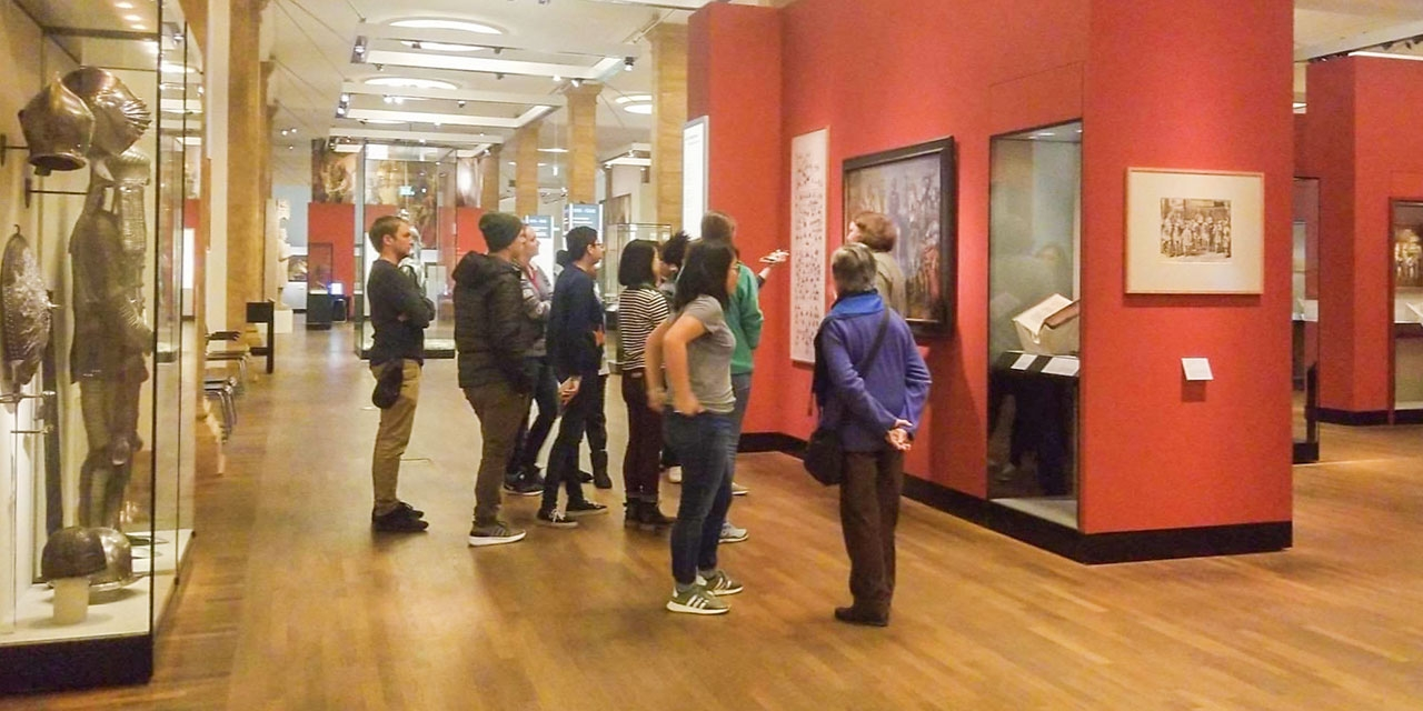 A group of female students stand looking at a painting on a red wall in the German Historical Museum.