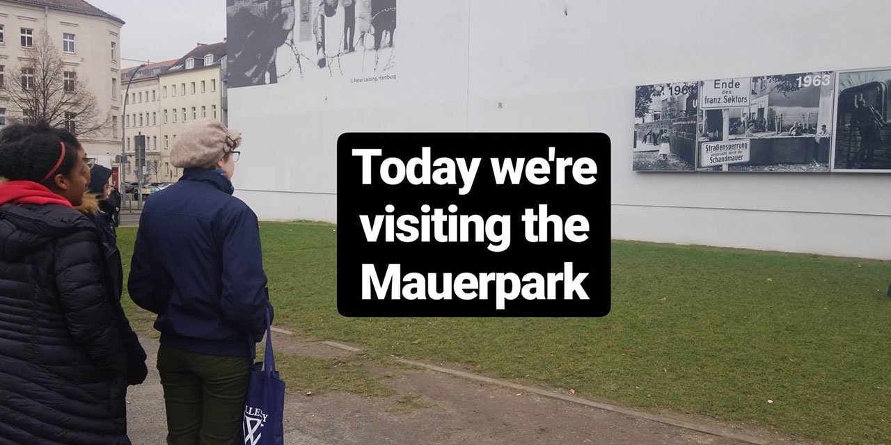Students outside at Mauerpark look at a long wall with black and white photos. Text reads, Today we're visiting the Mauerpark