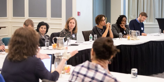 Faculty and staff sit at tables discussing diversity and inclusion at Wellesley