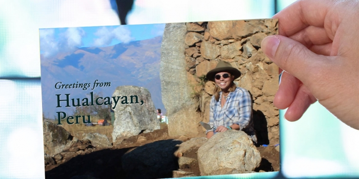 "A hand out of frame holds a postcard of a woman sitting at a dig site. It reads, ""Greetings from Hualcáyan, Peru."""