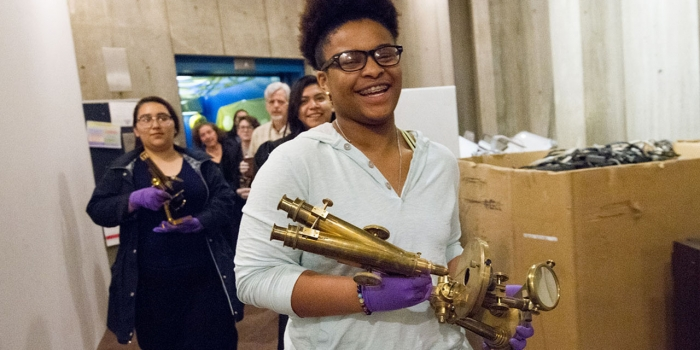 A line of students walk though the basement of the science building wearing purple gloves and holding brass microscopes.