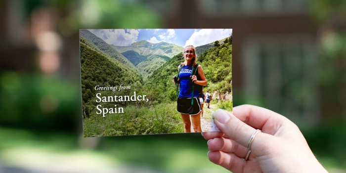 "A student stands in a Wellesley shirt in front of a mountain range in Spain. Text reads, ""Greetings from Santander, Spain"""